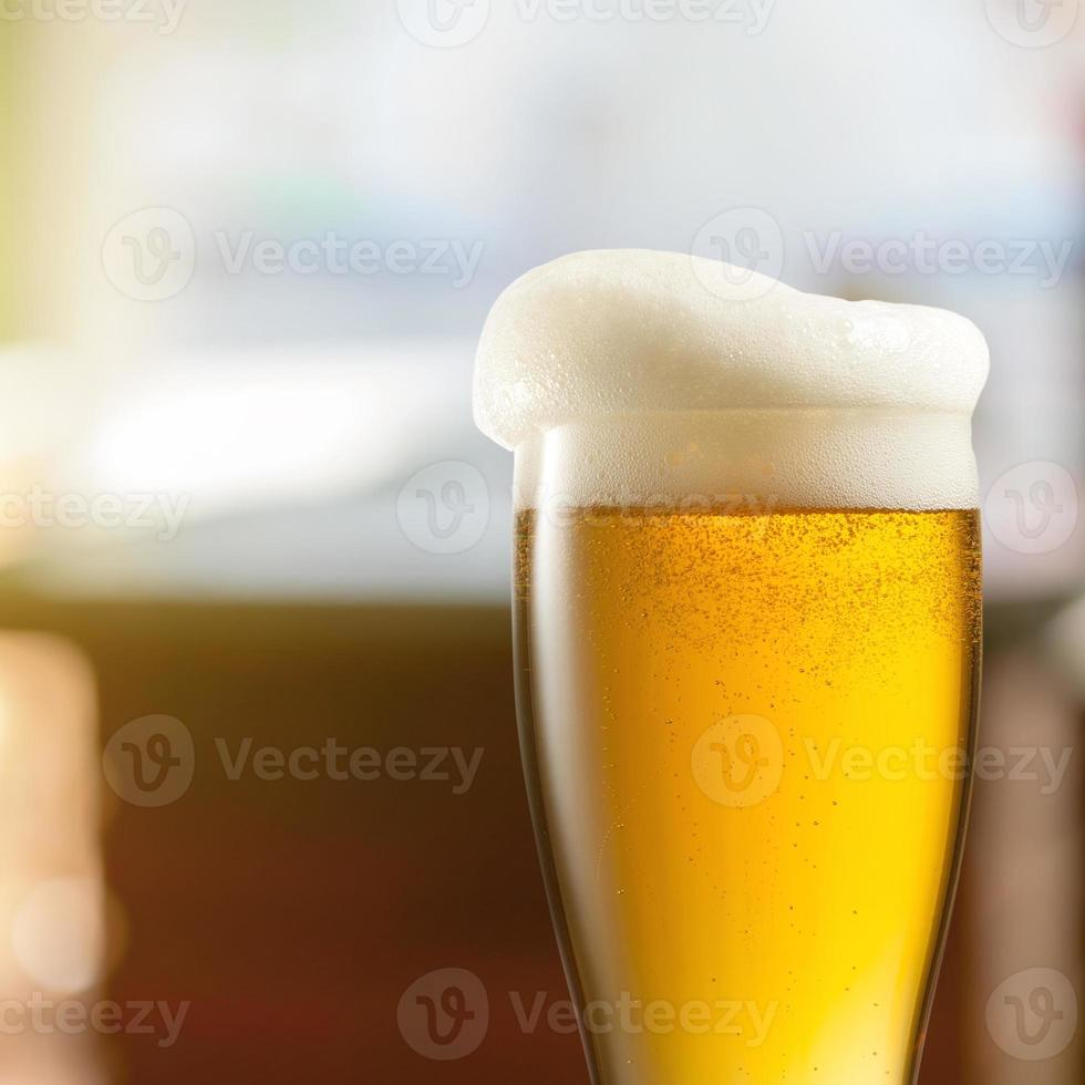 Glass of light beer in pub photo