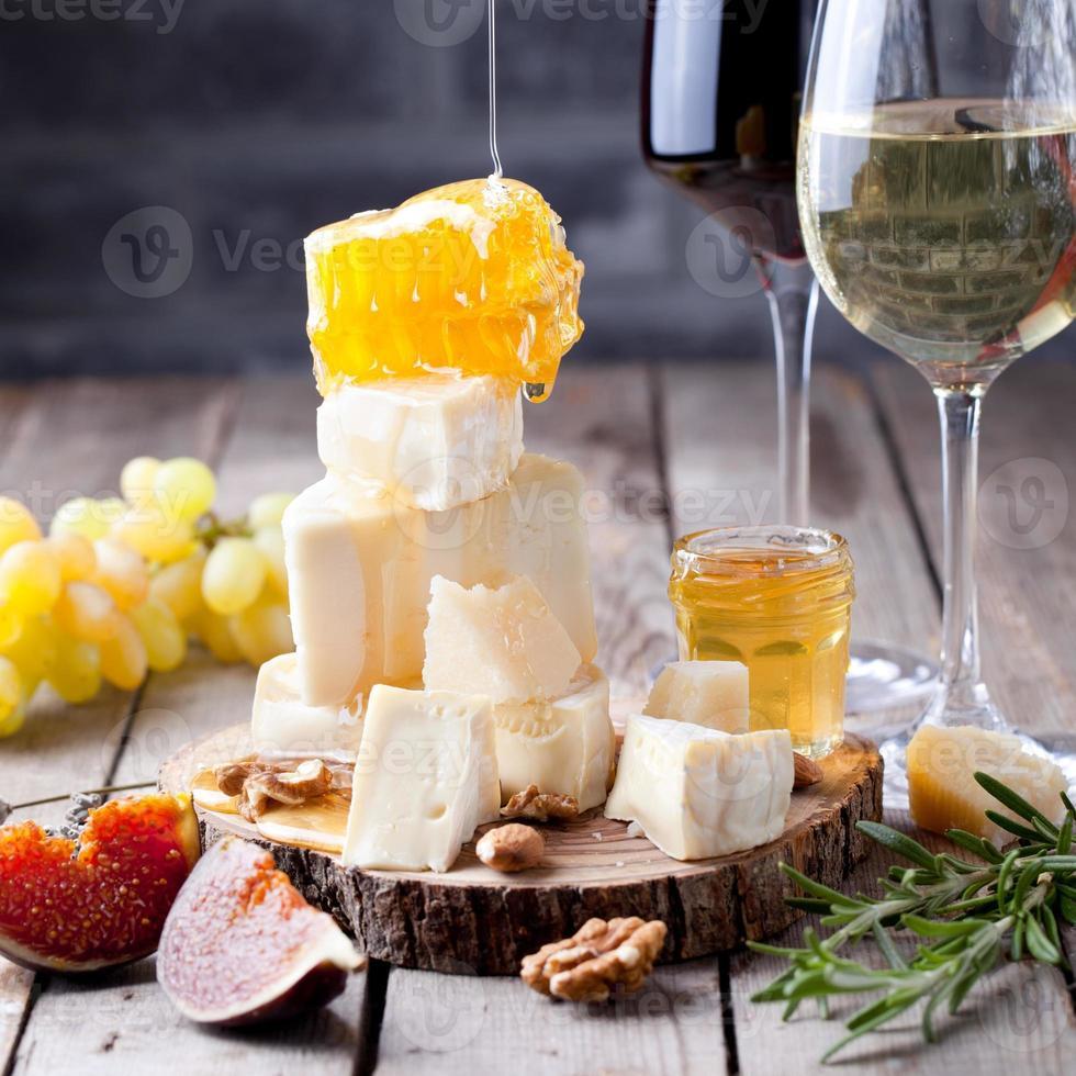 uva, queso, higos y miel con unas copas de vino. foto