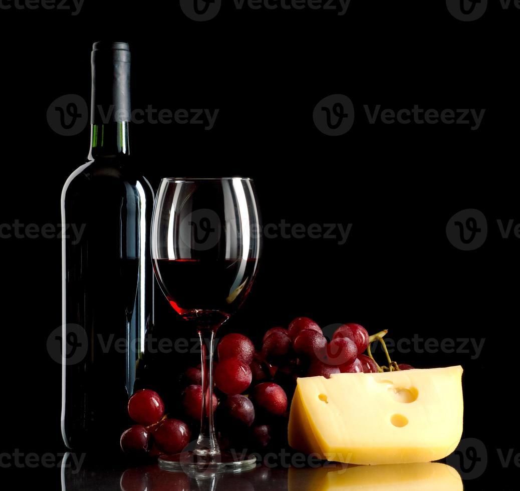 botella y copa de vino tinto con uvas y queso foto
