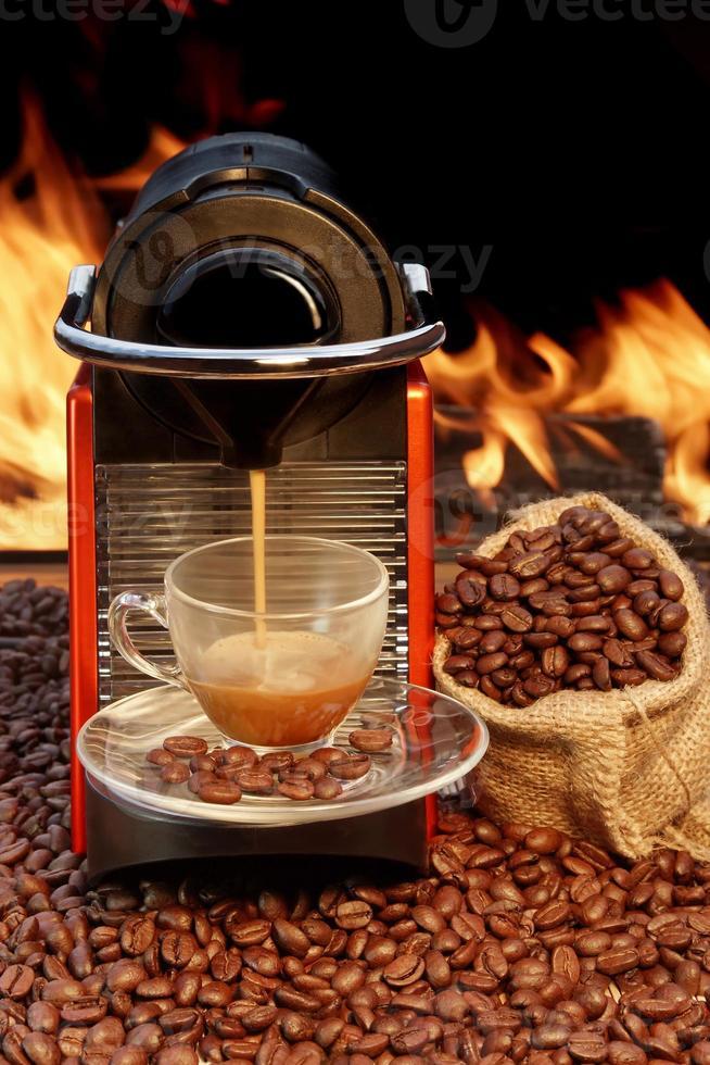 Coffee machine with cup  of espresso near fireplace photo