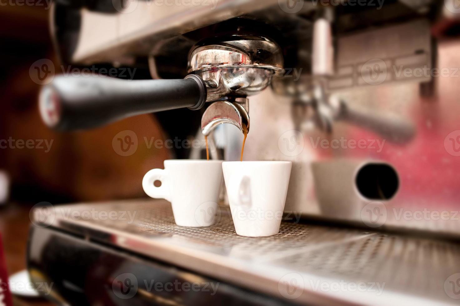 Máquina de espresso vertiendo café en tazas foto
