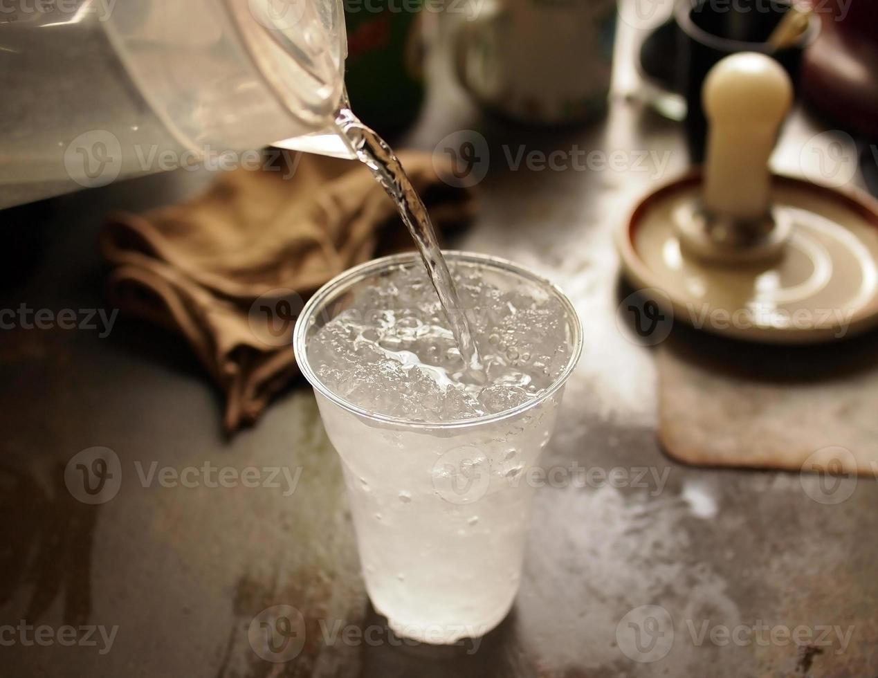 vertiendo agua fresca en un vaso de hielo foto
