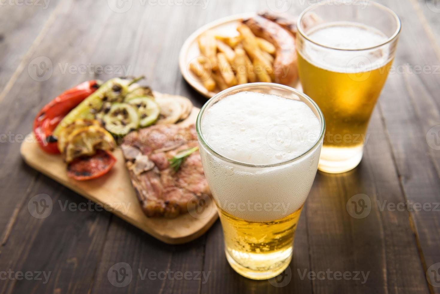 Beer in glass with gourmet steak and french fries photo