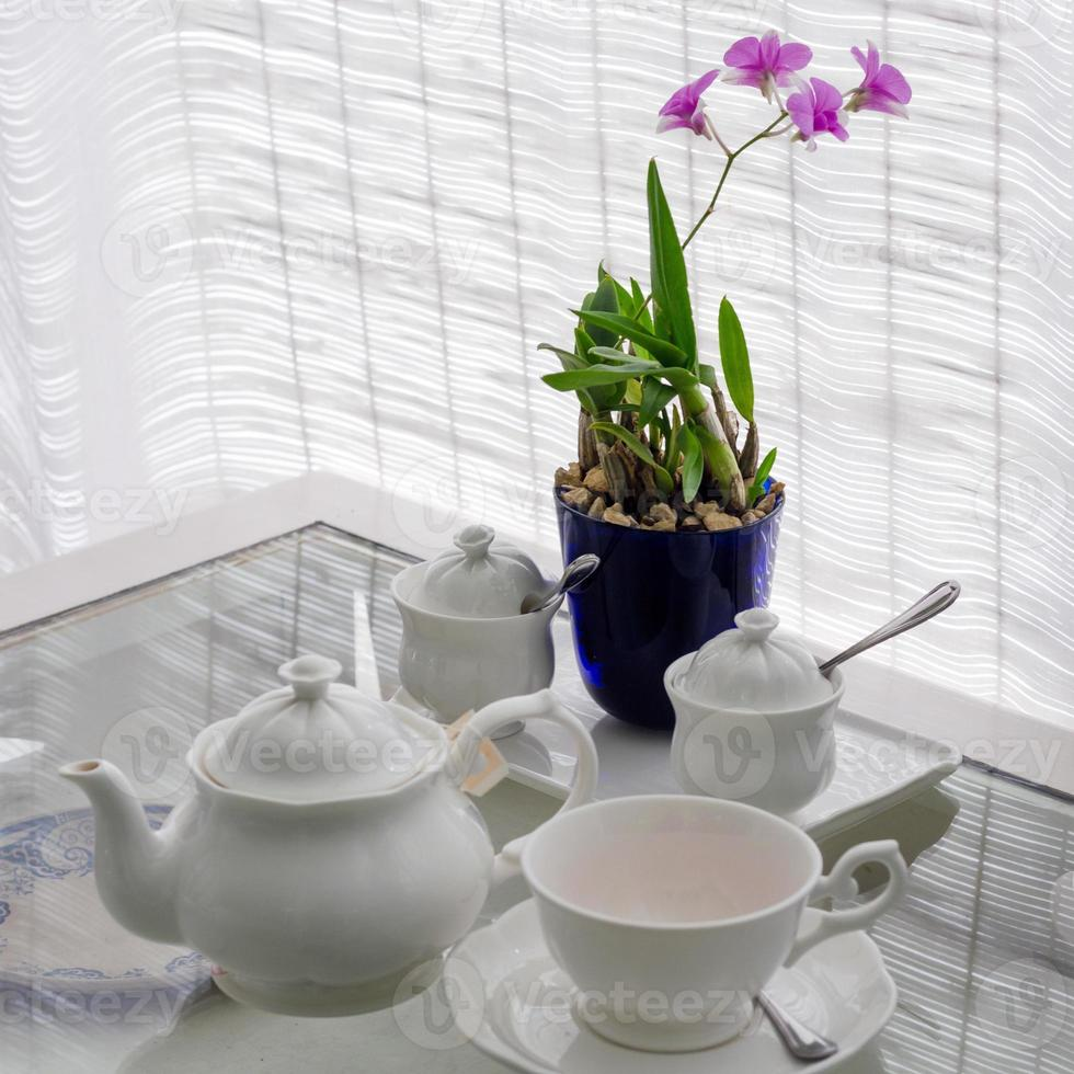 Ceramic utensils on table with flower decoration photo