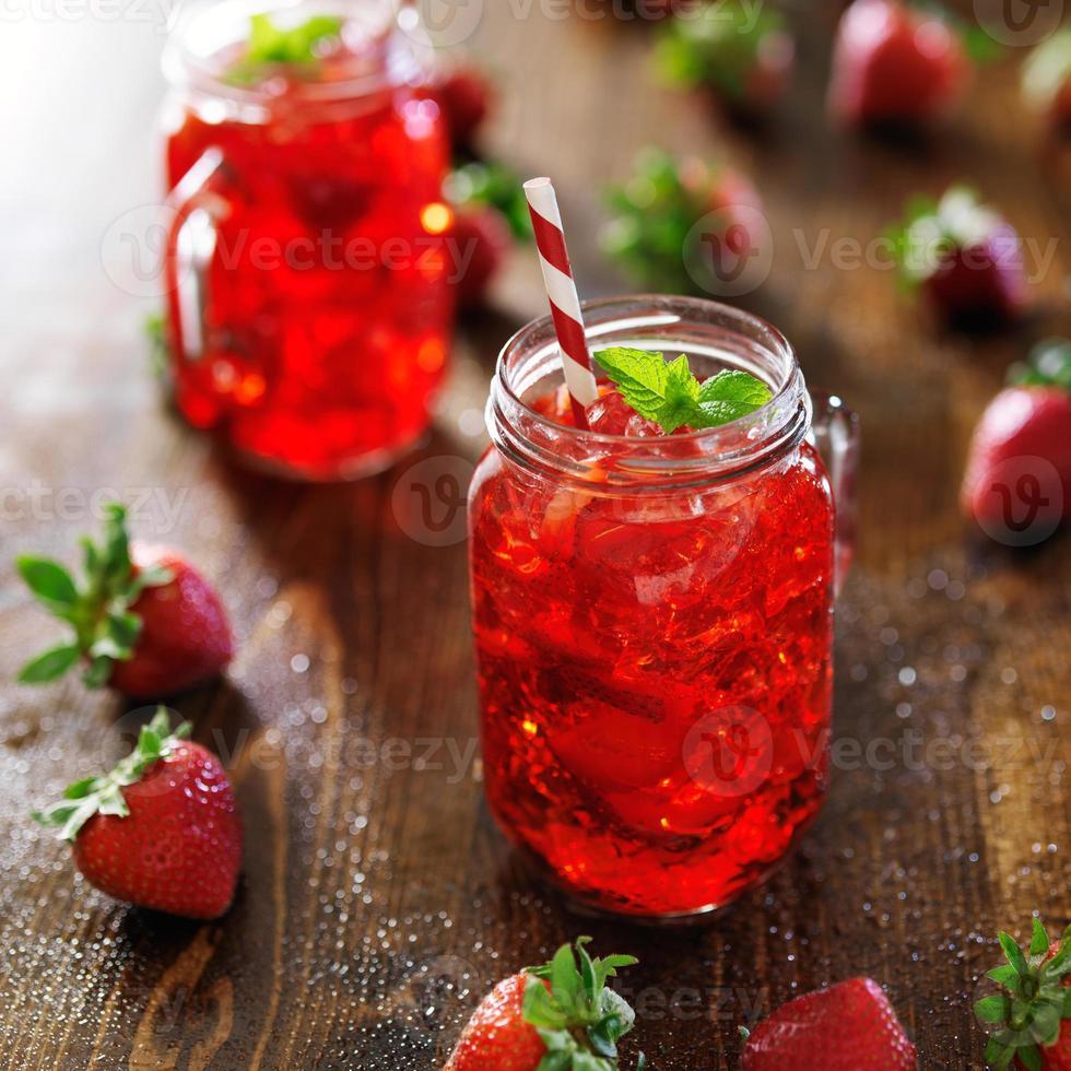 tarros de cristal con cóctel de fresa colorido foto