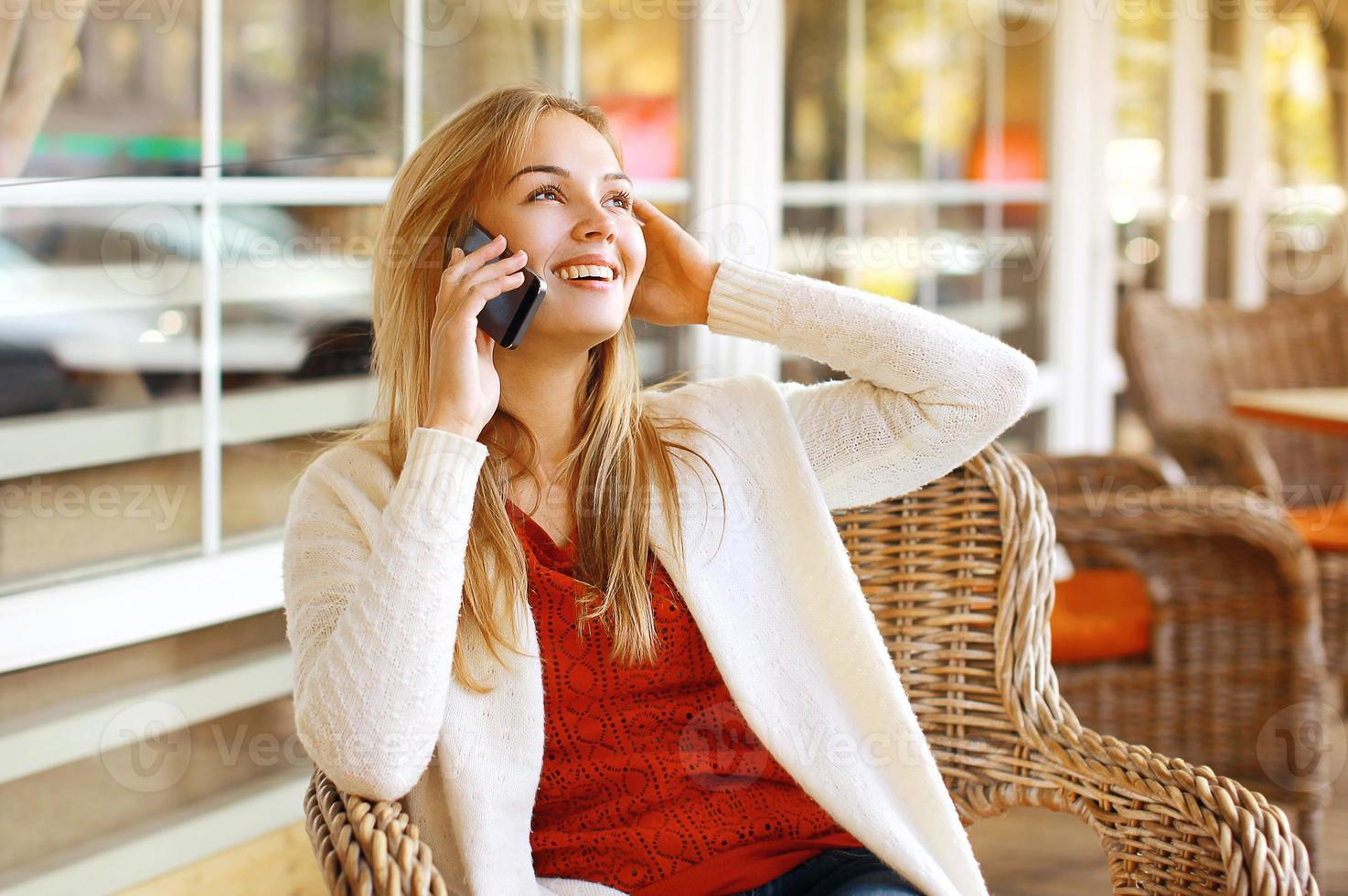 Pretty woman talking on the smartphone outdoors photo