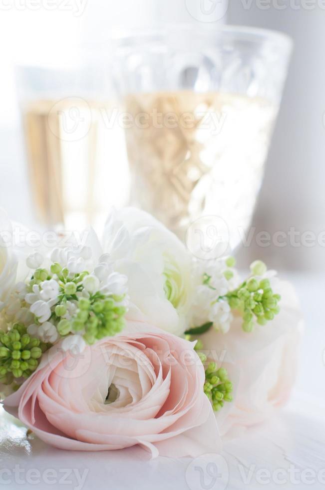 elegante ramo de flores y dos copas con vino foto
