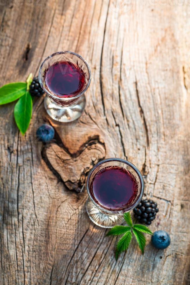 licor casero con alcohol y frutos rojos foto