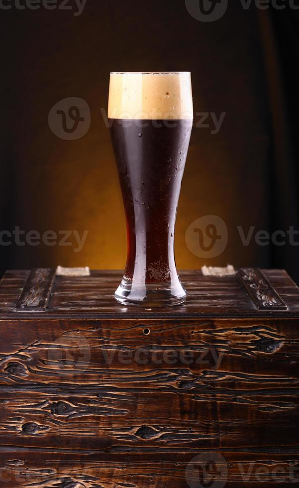 Glass of dark beer on a chest photo