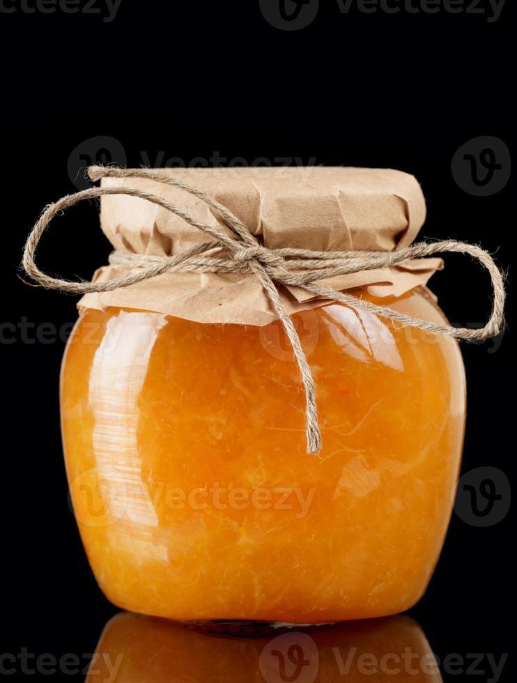 Gelatina de naranja en frasco de vidrio aislado en negro foto