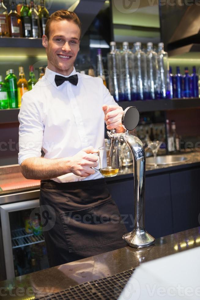 guapo barman tirando una pinta de cerveza foto
