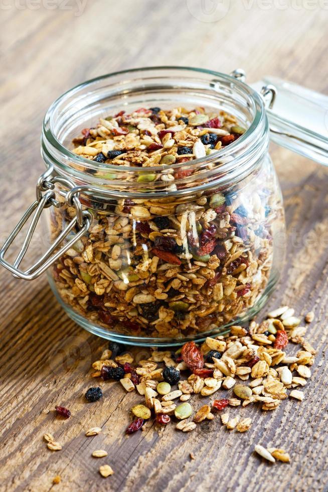 Homemade granola in open glass jar photo