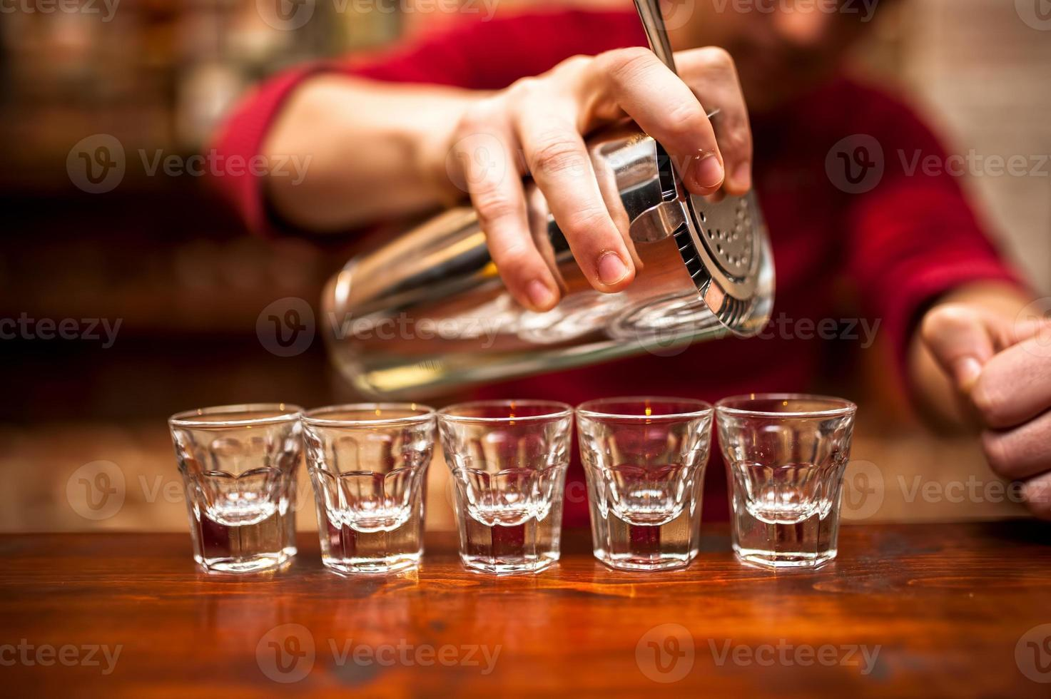 Primer plano de la mano del camarero vertiendo bebida alcohólica en la discoteca, foto