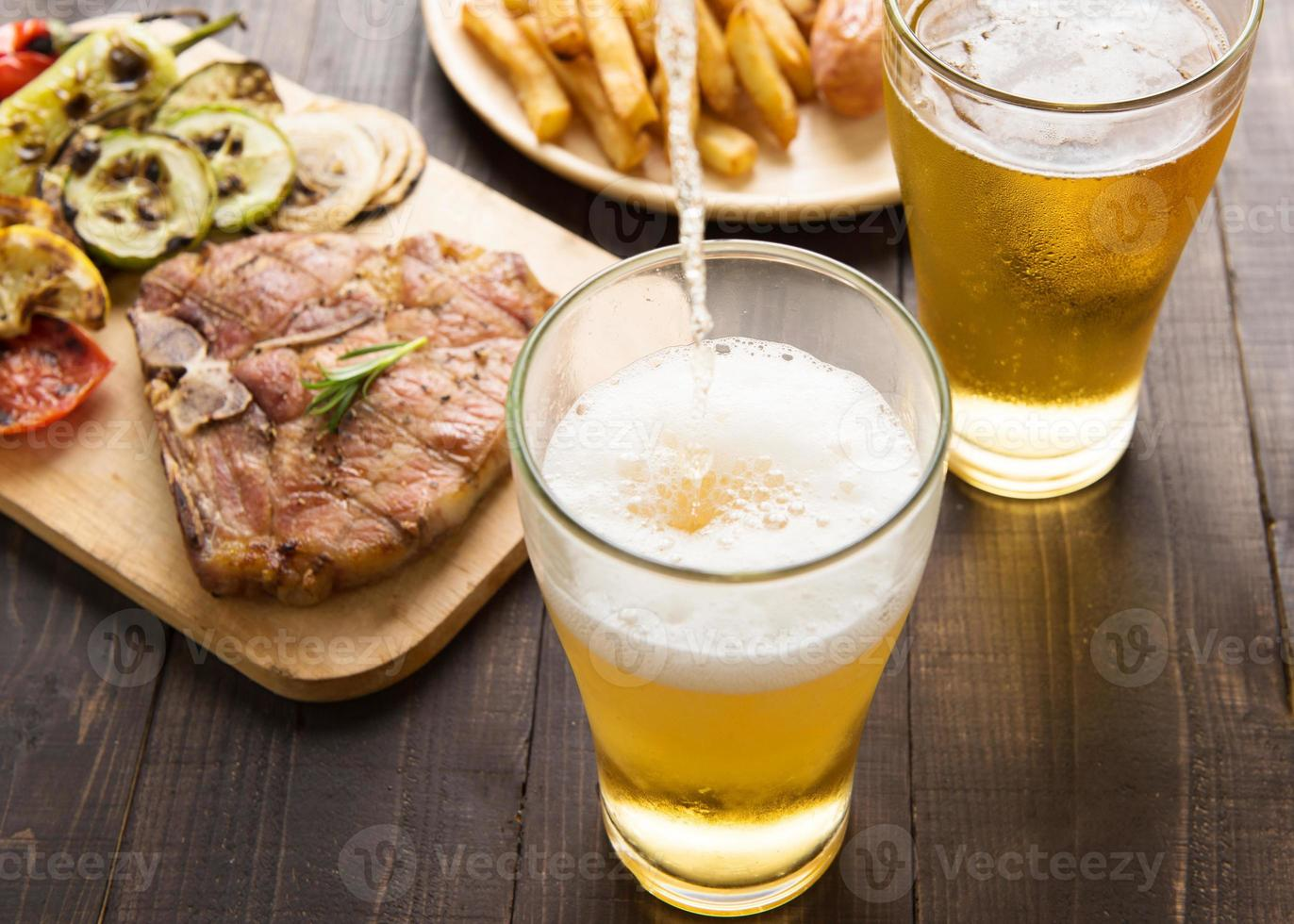 Beer being poured into glass with steak and french fries photo