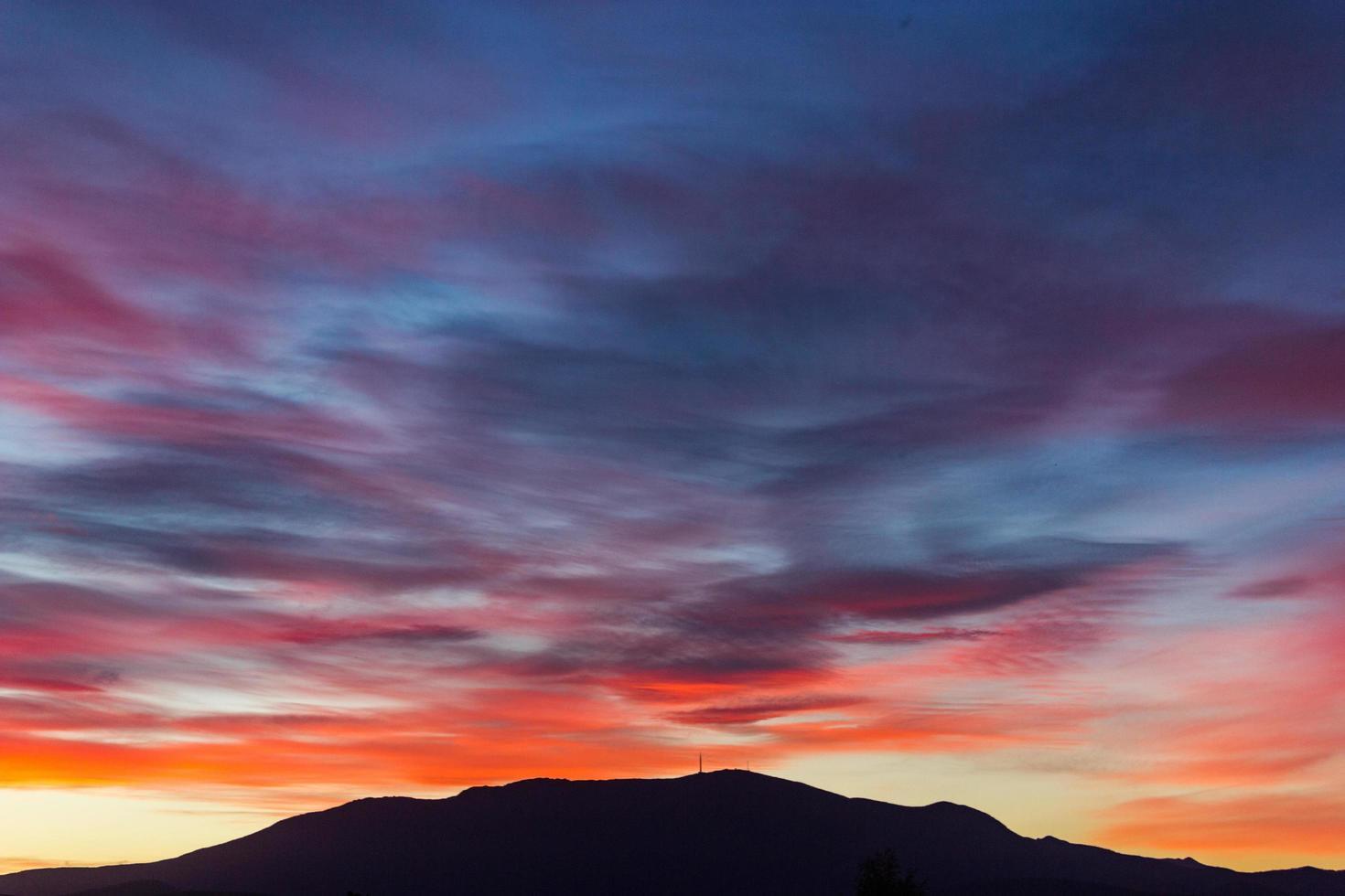 coloridas nubes al atardecer sobre la montaña foto