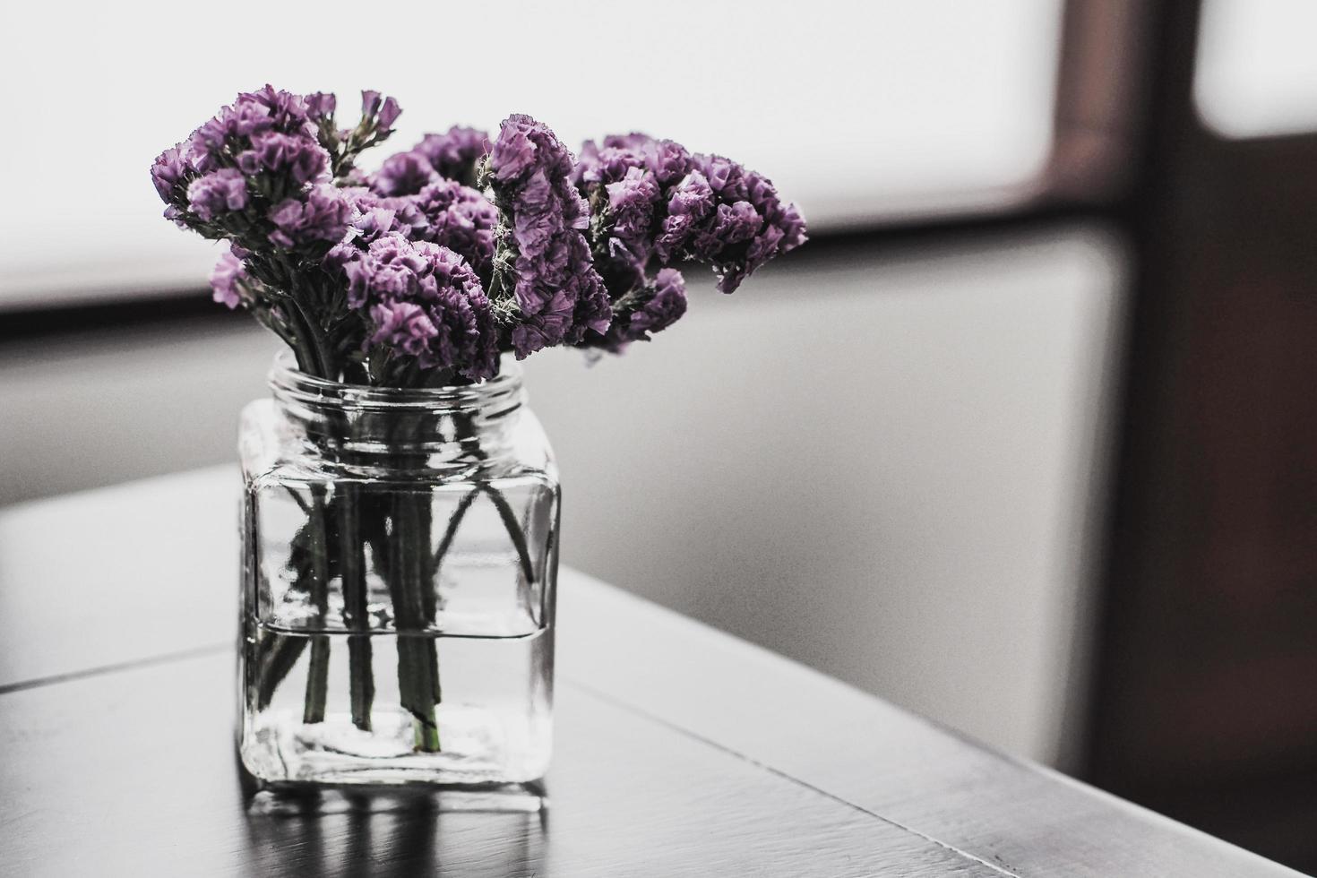 Violet flowers in glass vase photo