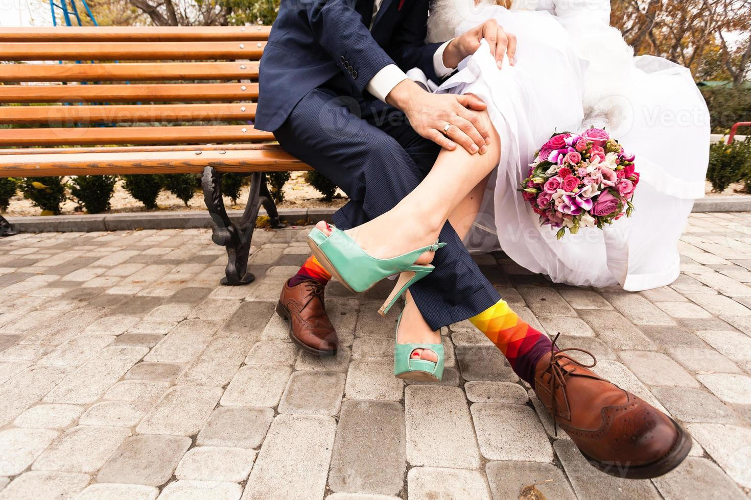 Bride and groom in bright clothes on the bench photo