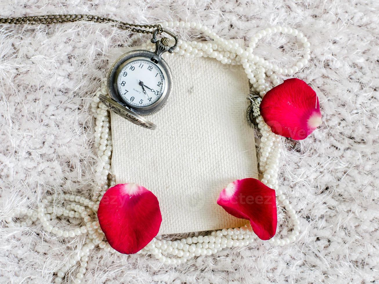Red rose, pearl, pocket watch and  mulberry paper notebook. photo