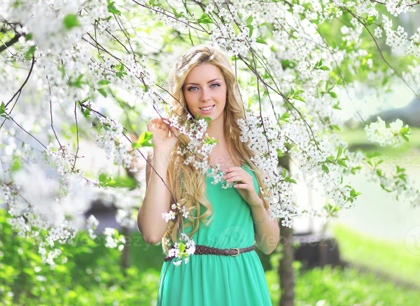 Cute girl in a spring day in floral garden photo