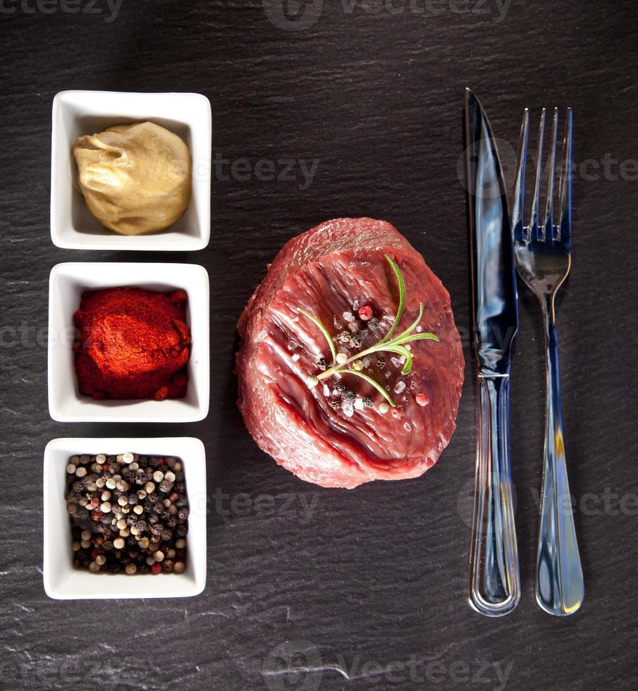 Fresh raw beef steak on black stone photo