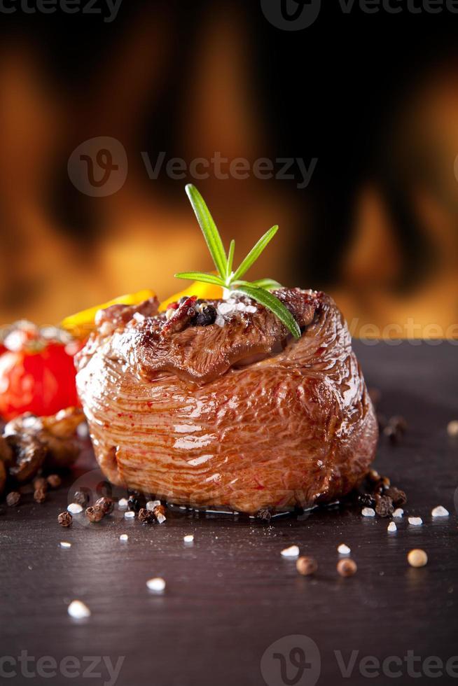 Filete de ternera fresca sobre piedra negra y fuego foto