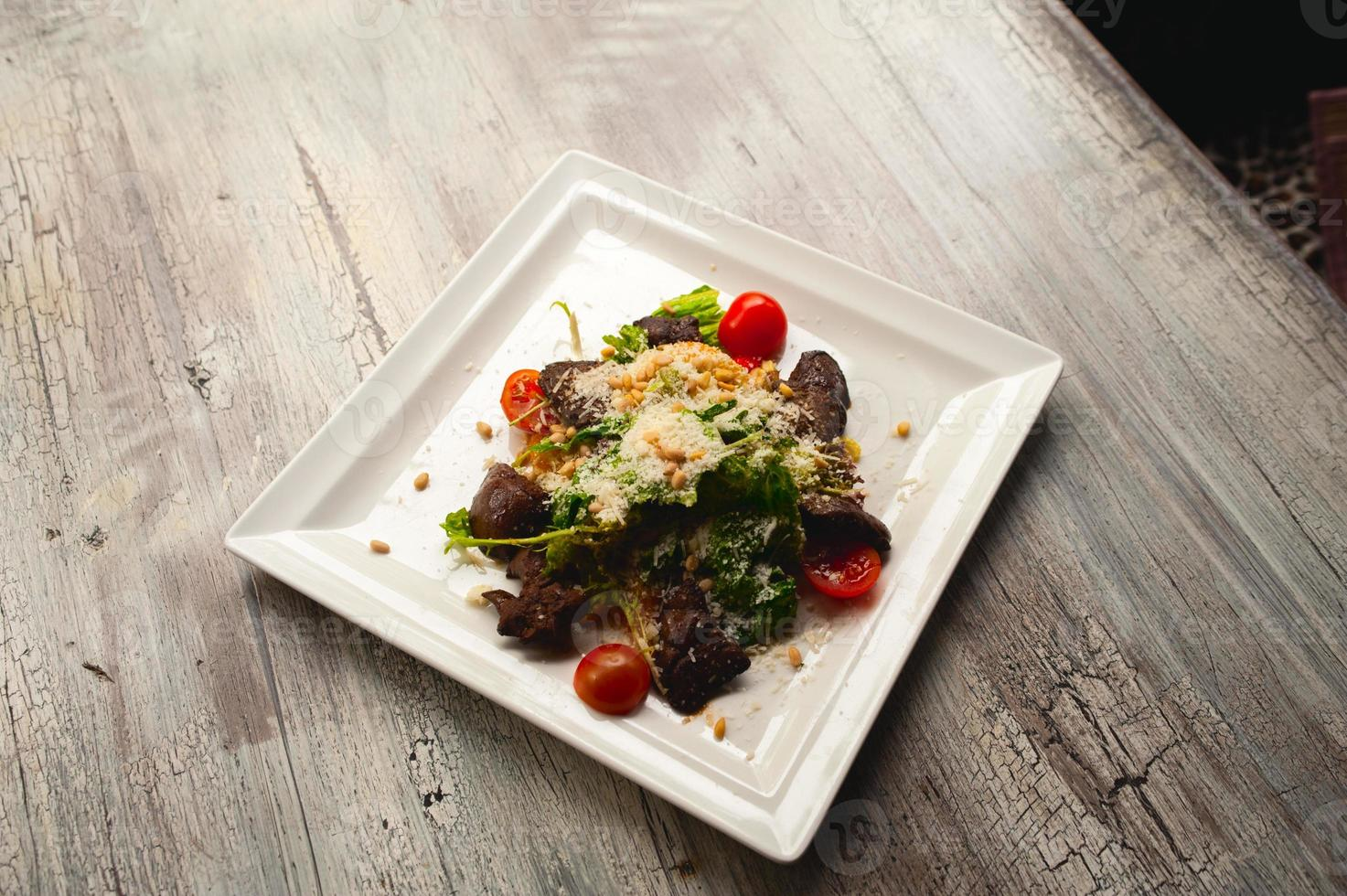 Caesar salad with meat, leafs and tomatoes on white plate photo
