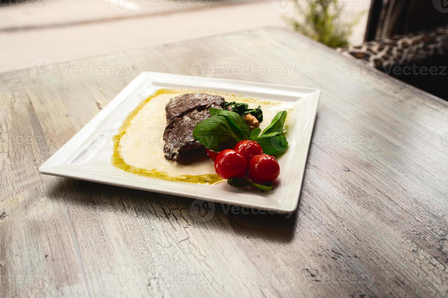 Grilled beef steak and mushrooms with tomatoes on wood table photo