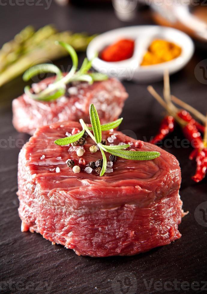 Filete de ternera cruda fresca sobre piedra negra foto