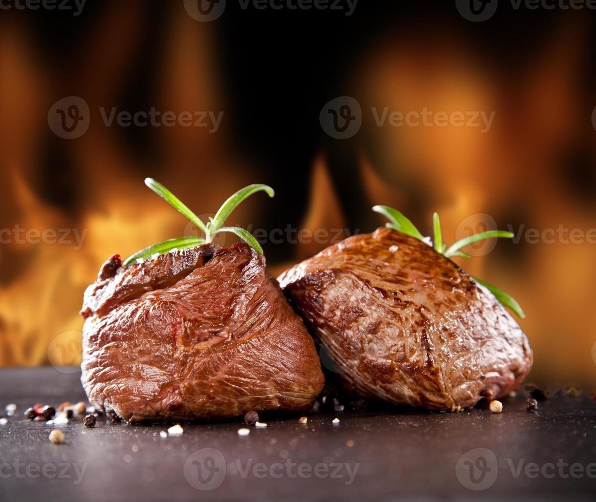 Filetes de ternera fresca sobre piedra negra y fuego. foto
