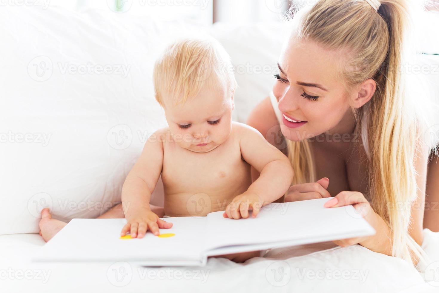 madre leyendo libro con bebe foto