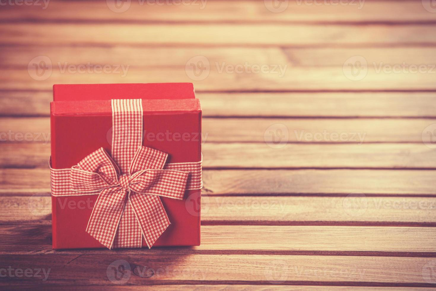 Red gift box on wooden table. photo
