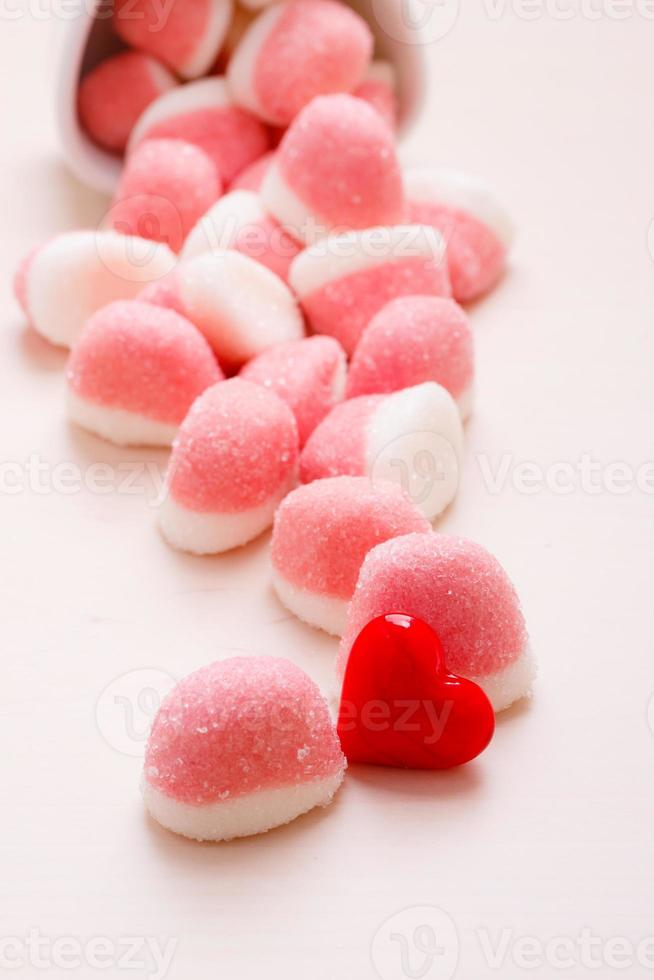 Pink jellies or marshmallows with sugar on table photo