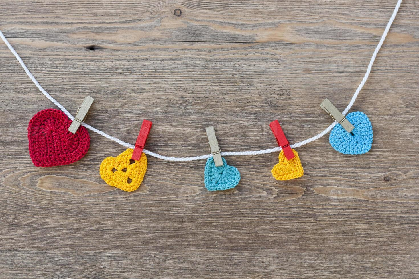Many multicolor crochet hearts on wooden background for Valentines day photo