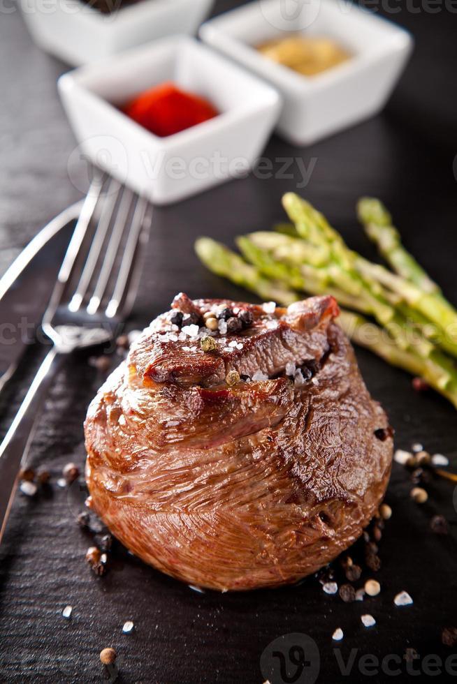 Fresh beef steak on black stone photo