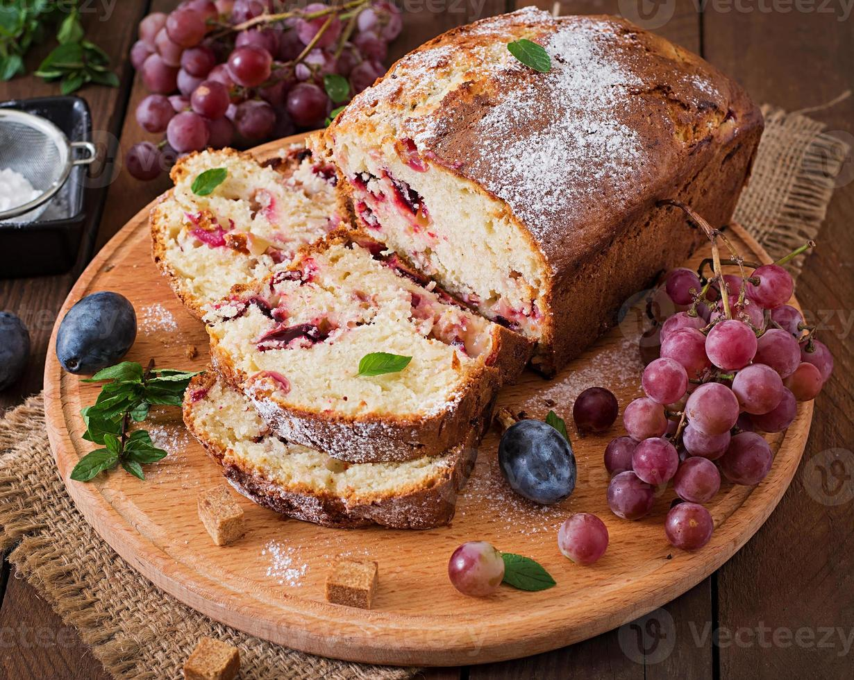Juicy and tender cupcake with plums and grapes photo