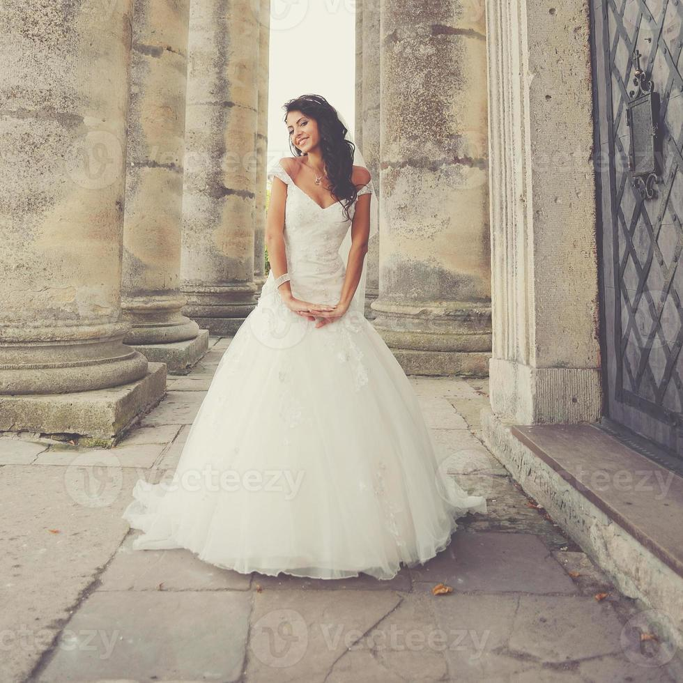 bride posing on the steps of an old church photo