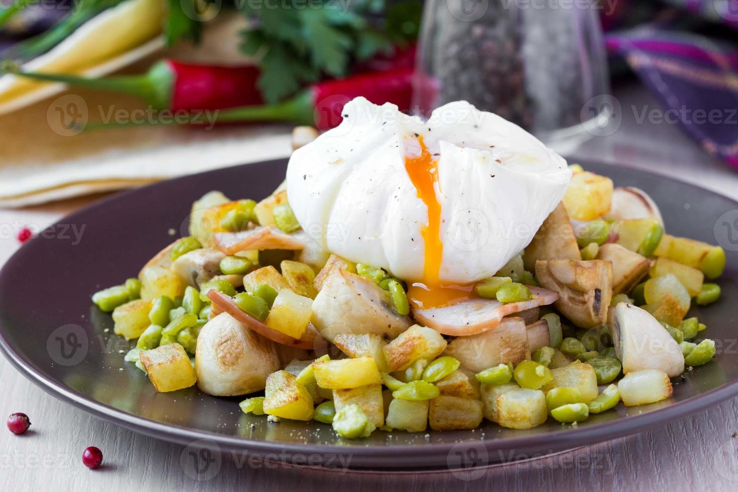 Hot salad with potatoes, ham, peas, mushrooms, poached egg photo