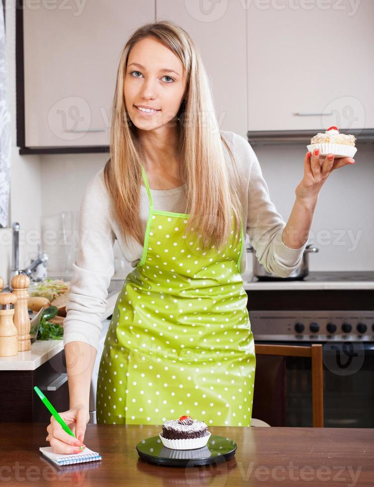 mujer en delantal pesando pasteles foto