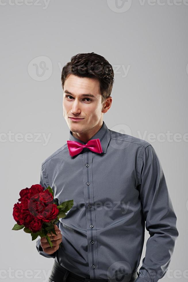 Handsome man holding red roses photo