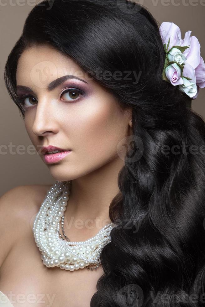 Hermosa mujer morena en la imagen de la novia con flores. foto