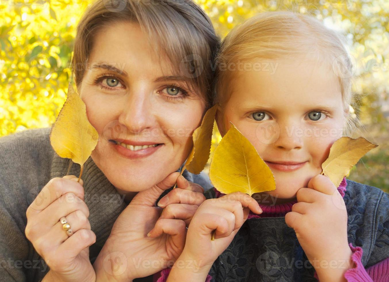 Autumn portrait of mother and daughter with yellow leaves photo
