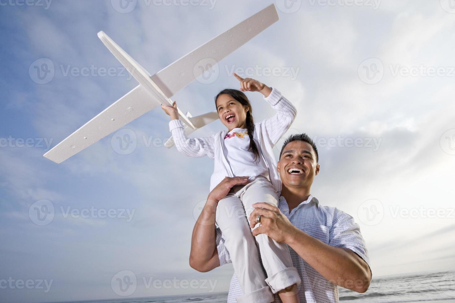 Papá hispano jugando sosteniendo a la niña en lo alto del hombro foto