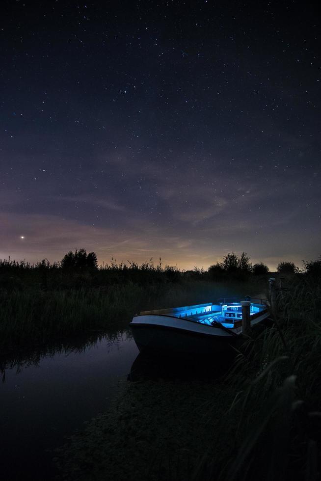 Blue and white boat illuminated on river  photo