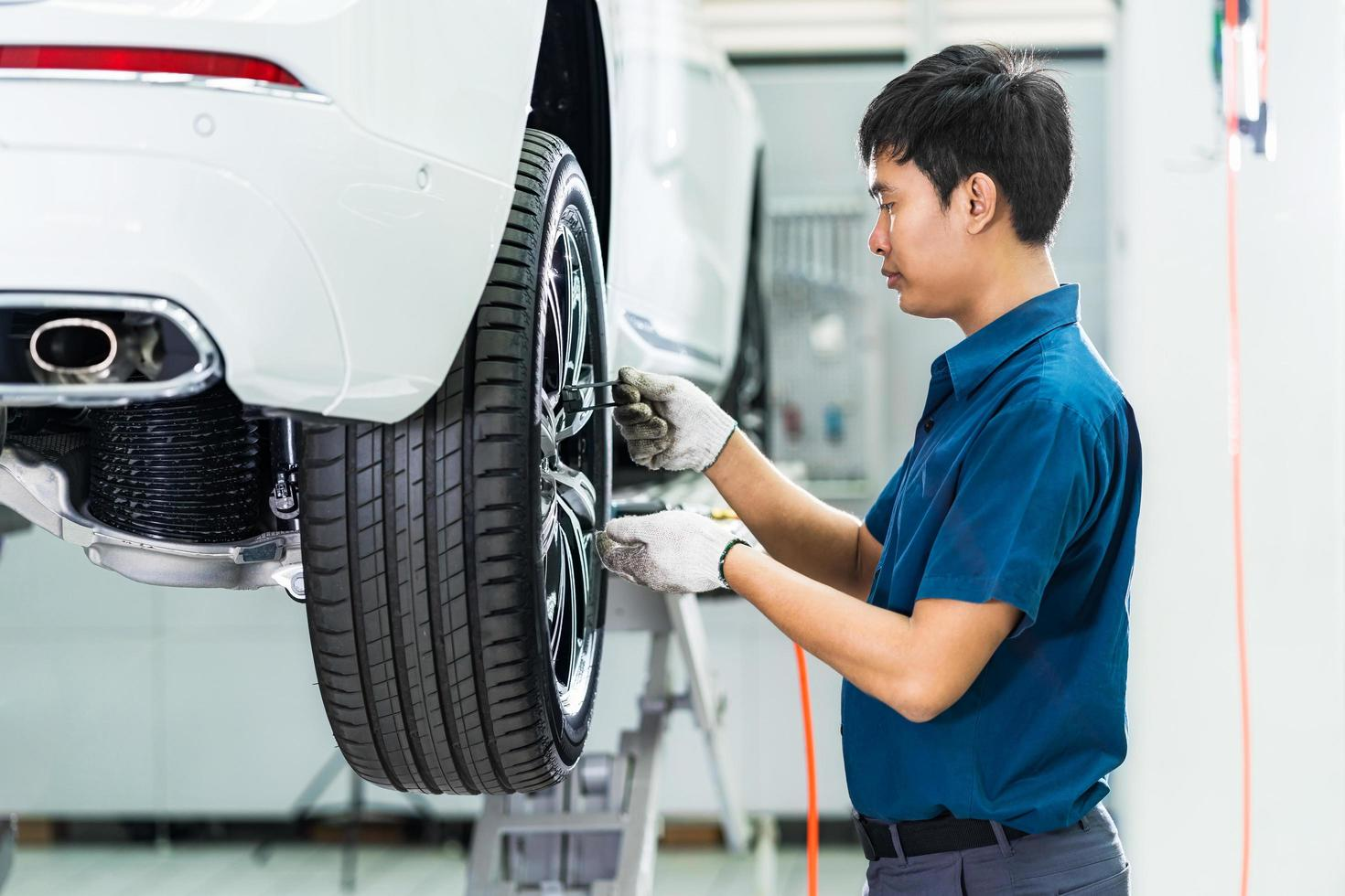 Asian mechanic checking car wheels photo