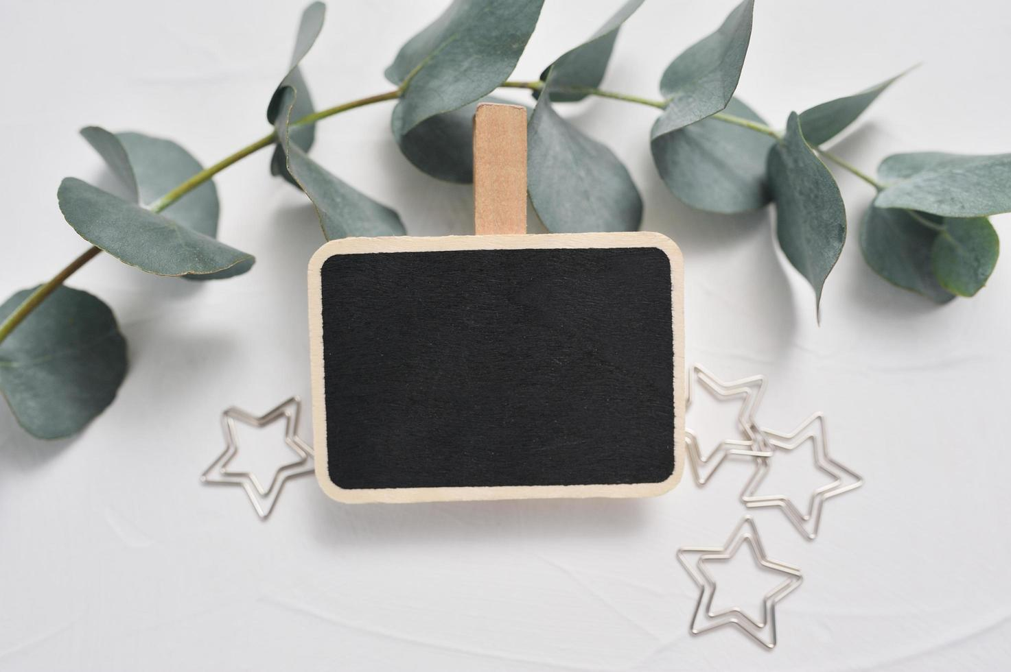 Mock up of eucalyptus branch, decor of stars and wooden board photo