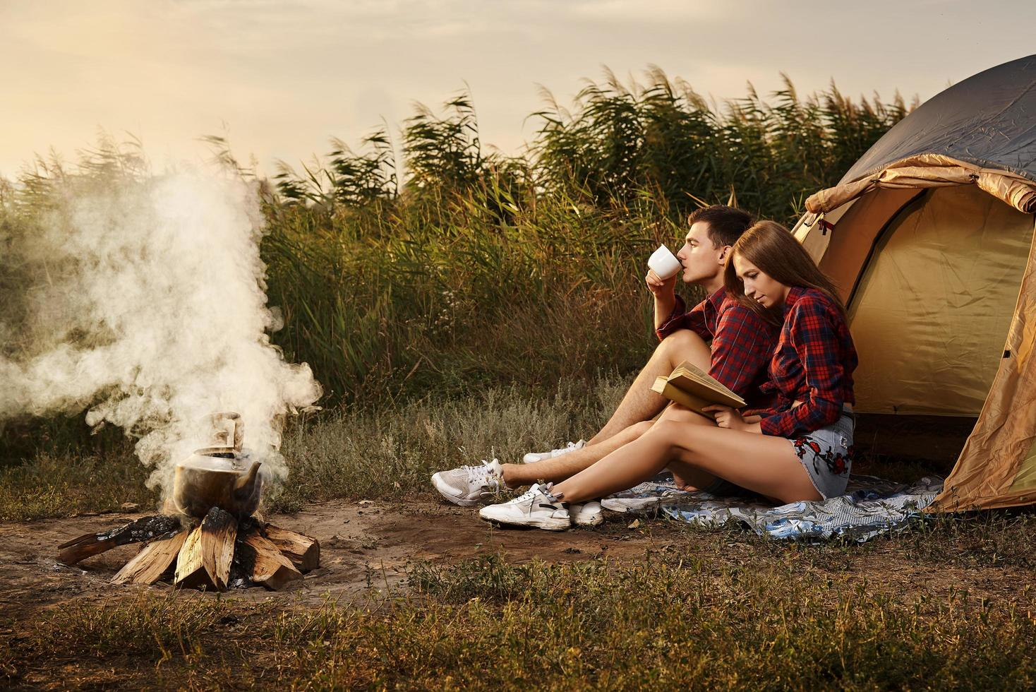 Young couple by fire at campsite photo