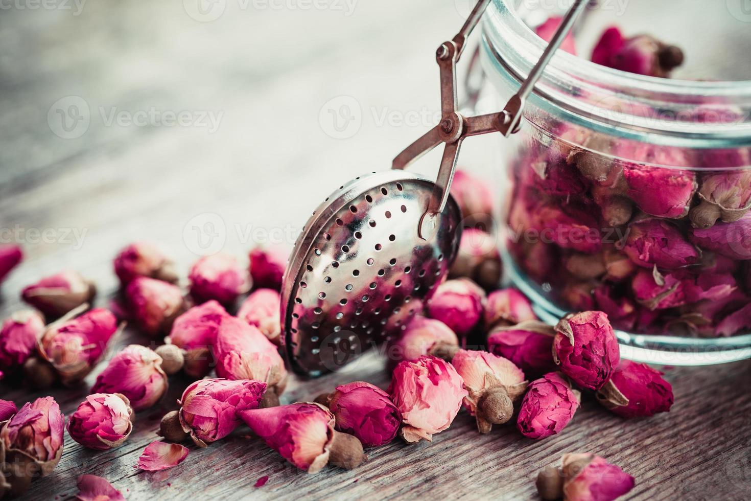 Rose buds tea, tea infuser and glass jar. photo