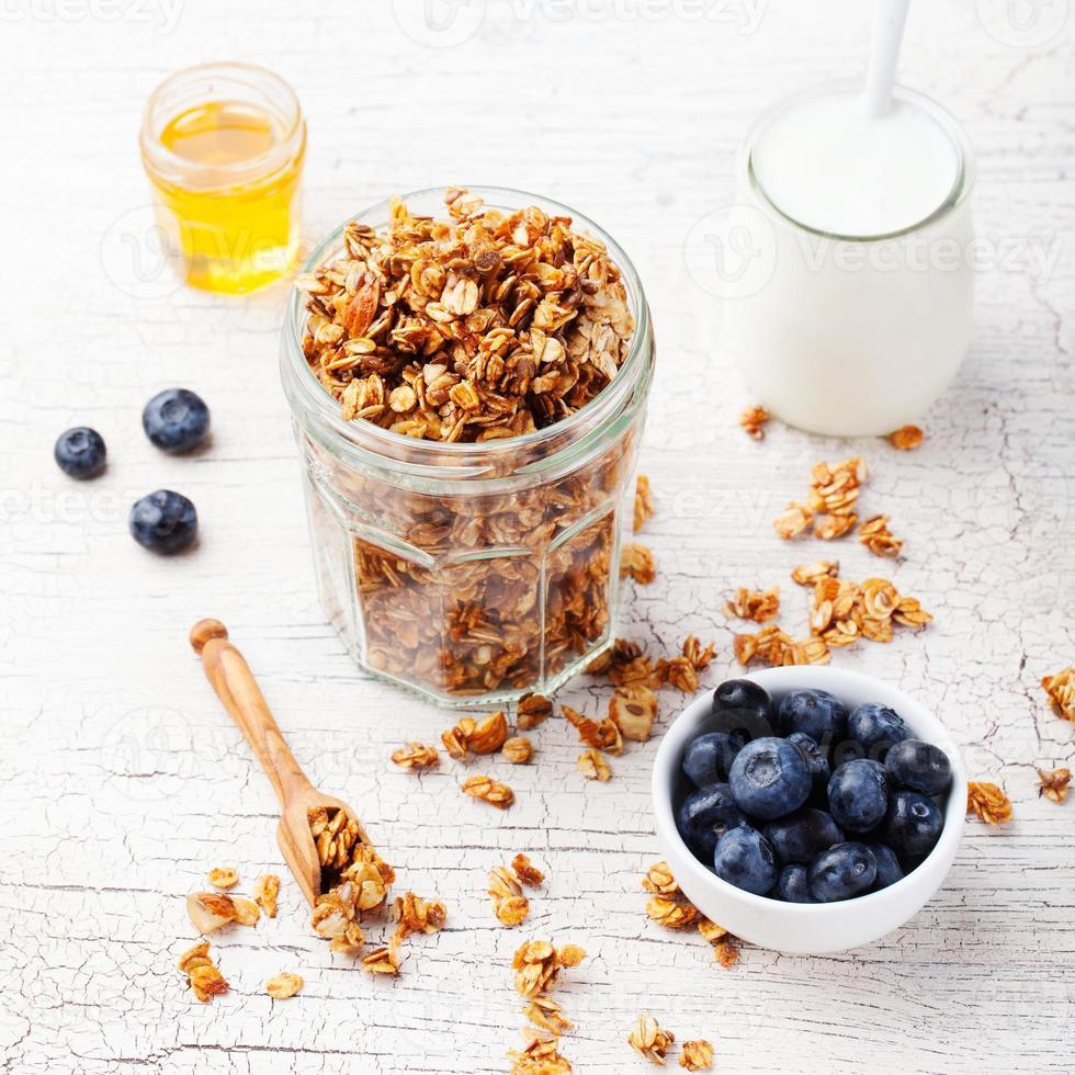 desayuno saludable. granola fresca, muesli con frutos rojos, miel foto