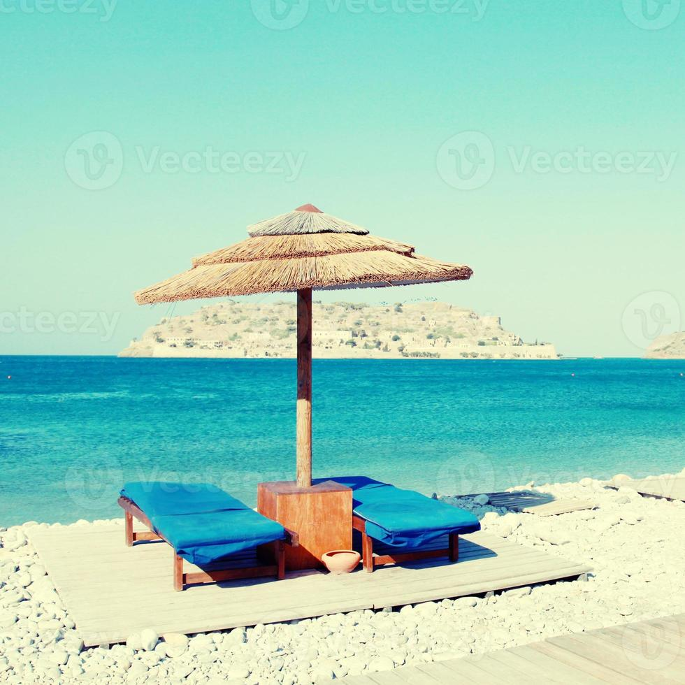 Sun beds on the beach of Mediterranean sea, Crete photo