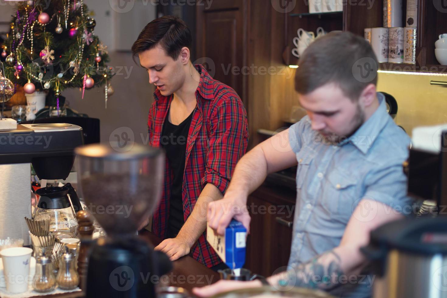 Two hipsters working in a coffee shop making orders cleaning photo